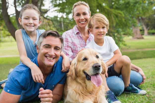 papa,mama,hijo e hija felices en el cesped con el perro de la familia